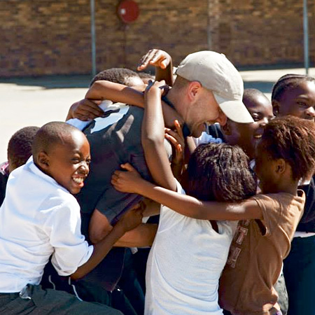 Student hugged by South African community children