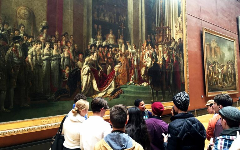 Students admiring large paintings