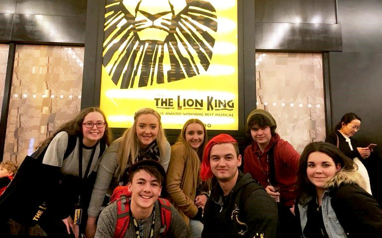 Students in front of poster for The Lion King musical