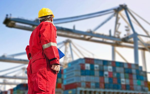 Man in construction uniform looking over shipping containers
