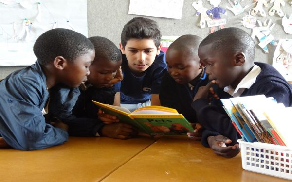 Boy reading to group of young students Service learning tour Cape Town South Africa