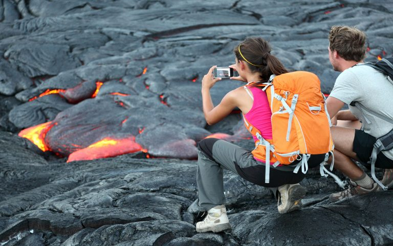 Students taking photos of small lava stream